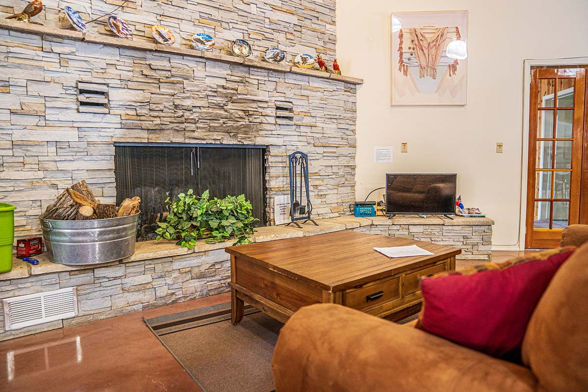 Sitting area by fireplace in Lamplighter RV Resort & Park's Clubhouse