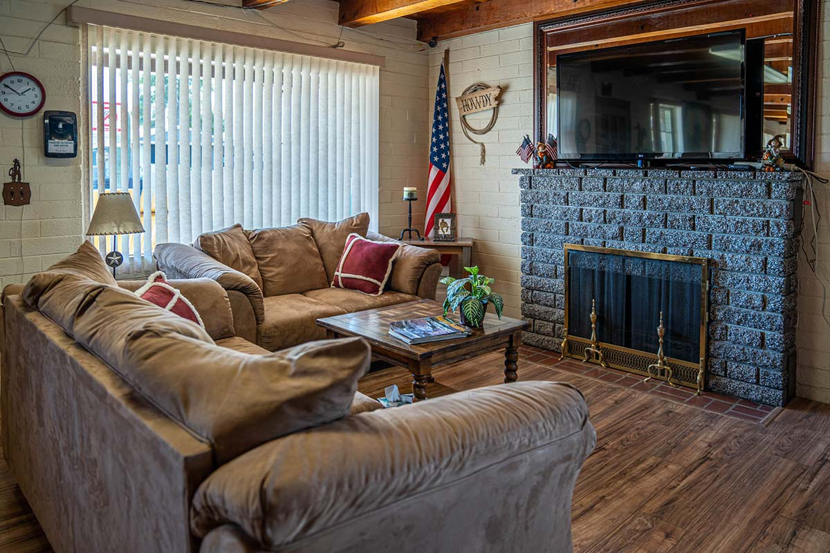 Comfy seating around fireplace and mounted TV in the clubhouse