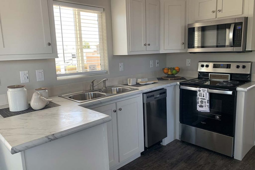 Bright kitchen with white cabinets and black and stainless steel appliances
