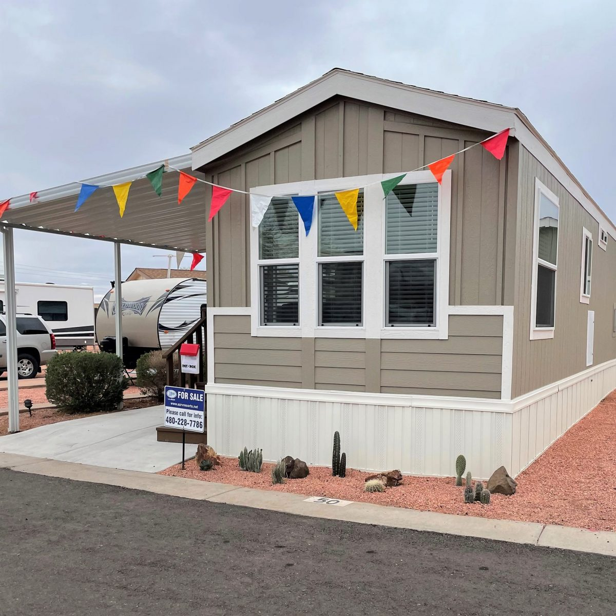 Mobilehome on redrock lot with cacti, for sale sign