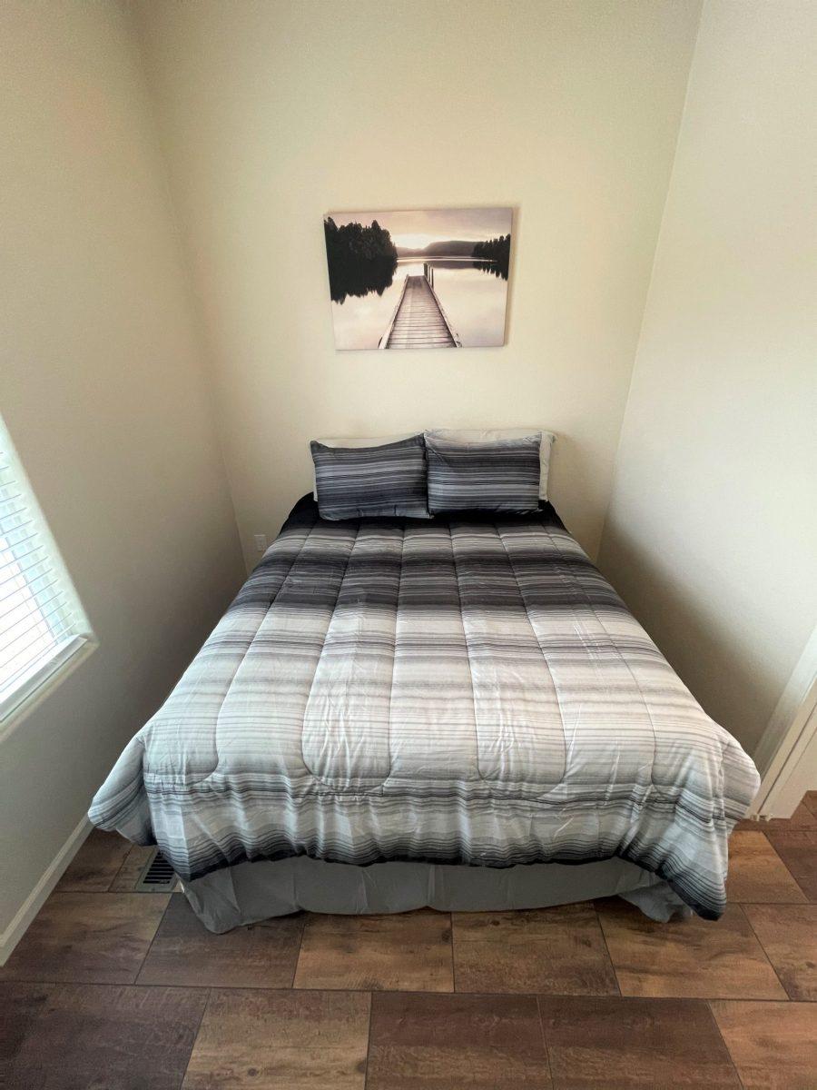 BED in bedroom with dark wood-laminate flooring