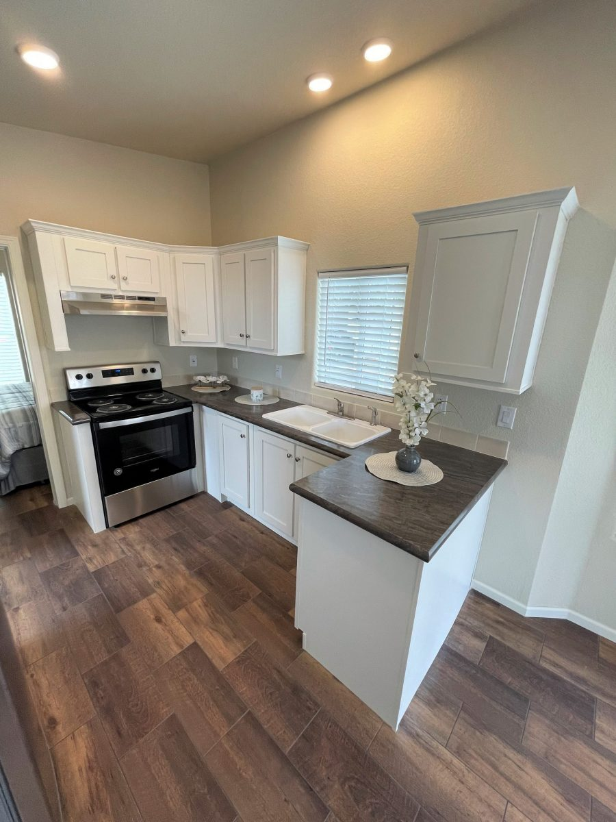 KITCHEN with brown wood-laminate flooring, white cabinetry, dark marble-style laminate countertops, short white tile backsplash, window w/ blinds, black/steel oven/range