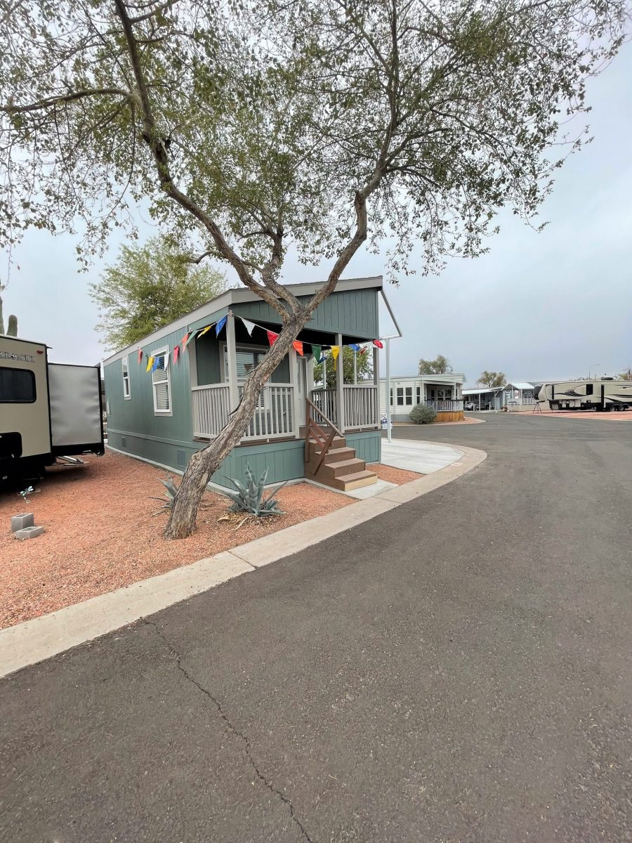 Green Manufactured home on redrock landscaped lot with tree and bushes