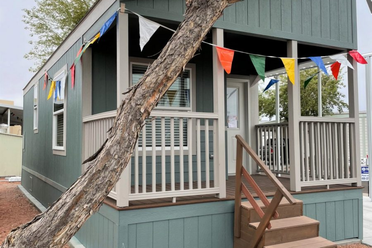 Green Manufactured Home on redrock lot with tree and bushes