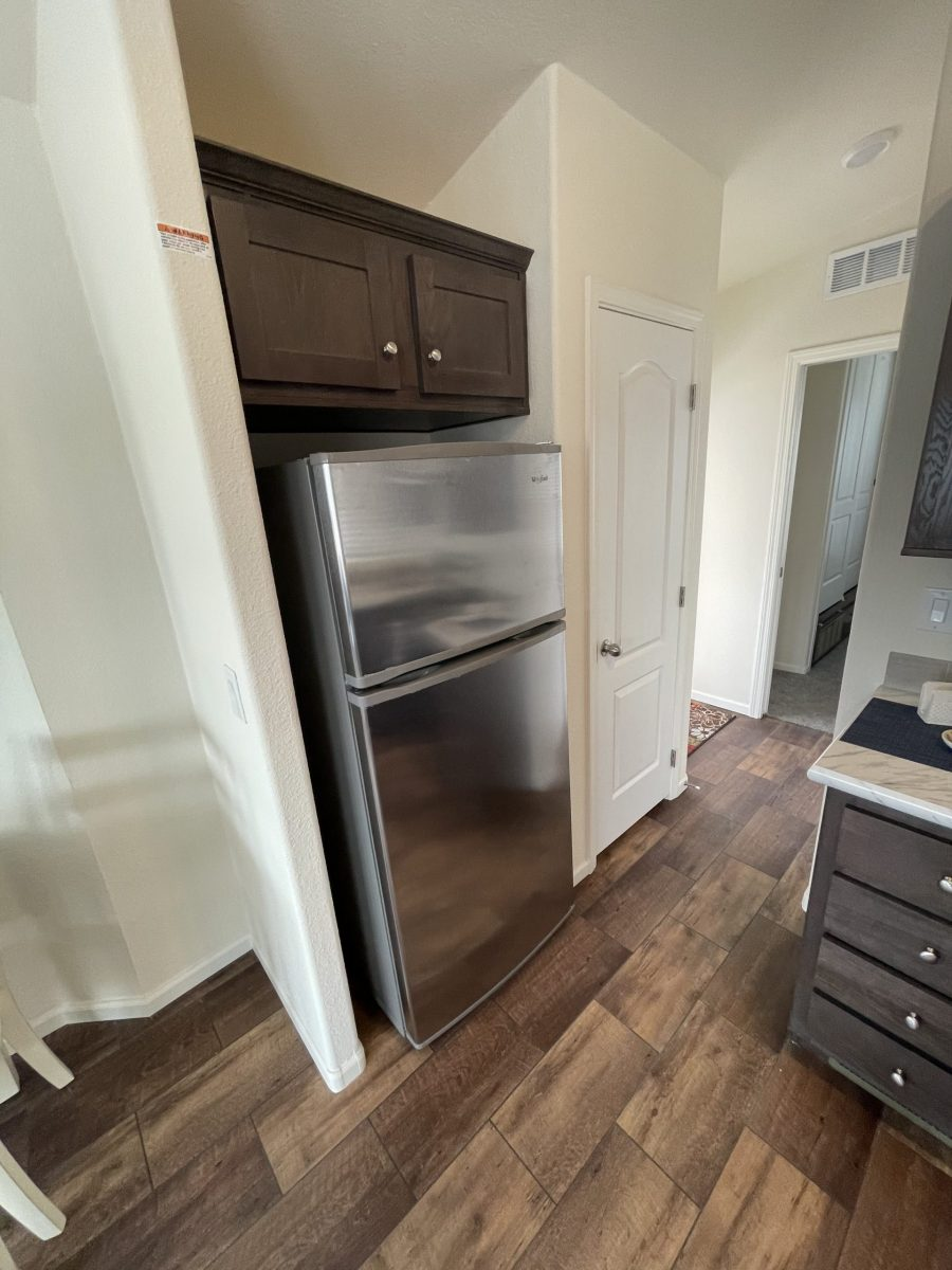 Fridge and pantry in kitchen with dark cabinetry and brown wood-laminate floors