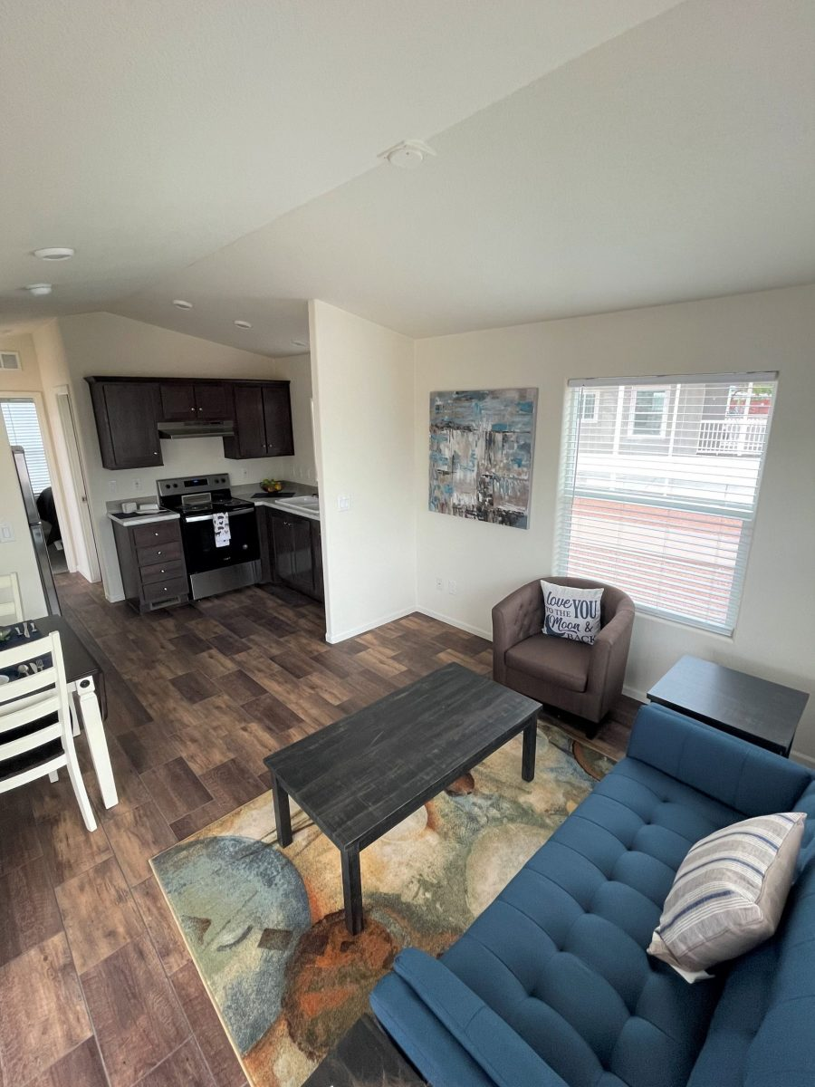 Furnished livingroom, kitchen in background, dark cabinetry, woodlaminate floors