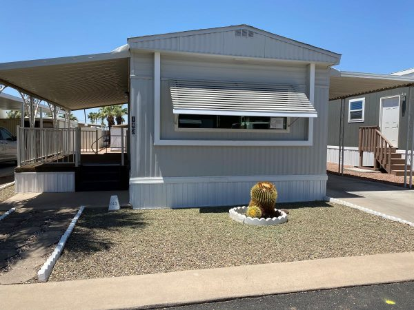 Mobile home with 2 awnings, concrete carport, raised & carpeted patio, desert landscape yard with cactus