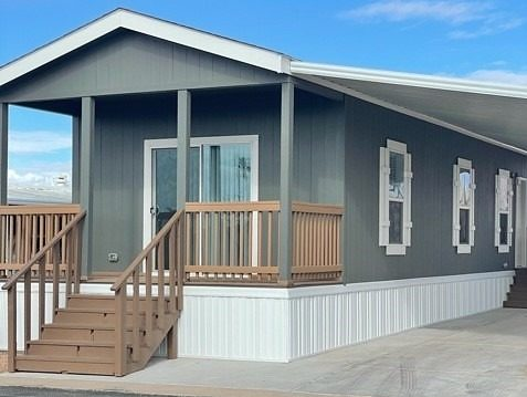 manufactured home with concrete drive custom awning raised porch, sliding glass door