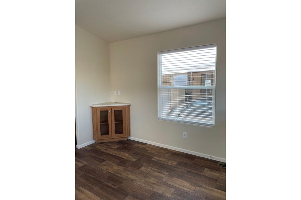 built in livingroom corner cabinet and window, brown wood-laminate flooring