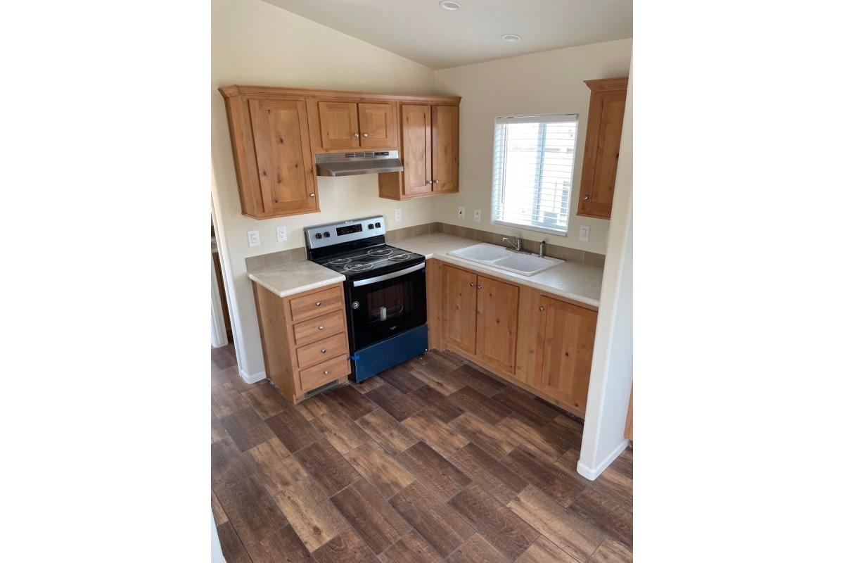 Kitchen with window at sink, laminate countertop with short backsplash, black/chrome oven/range, wood cabinets