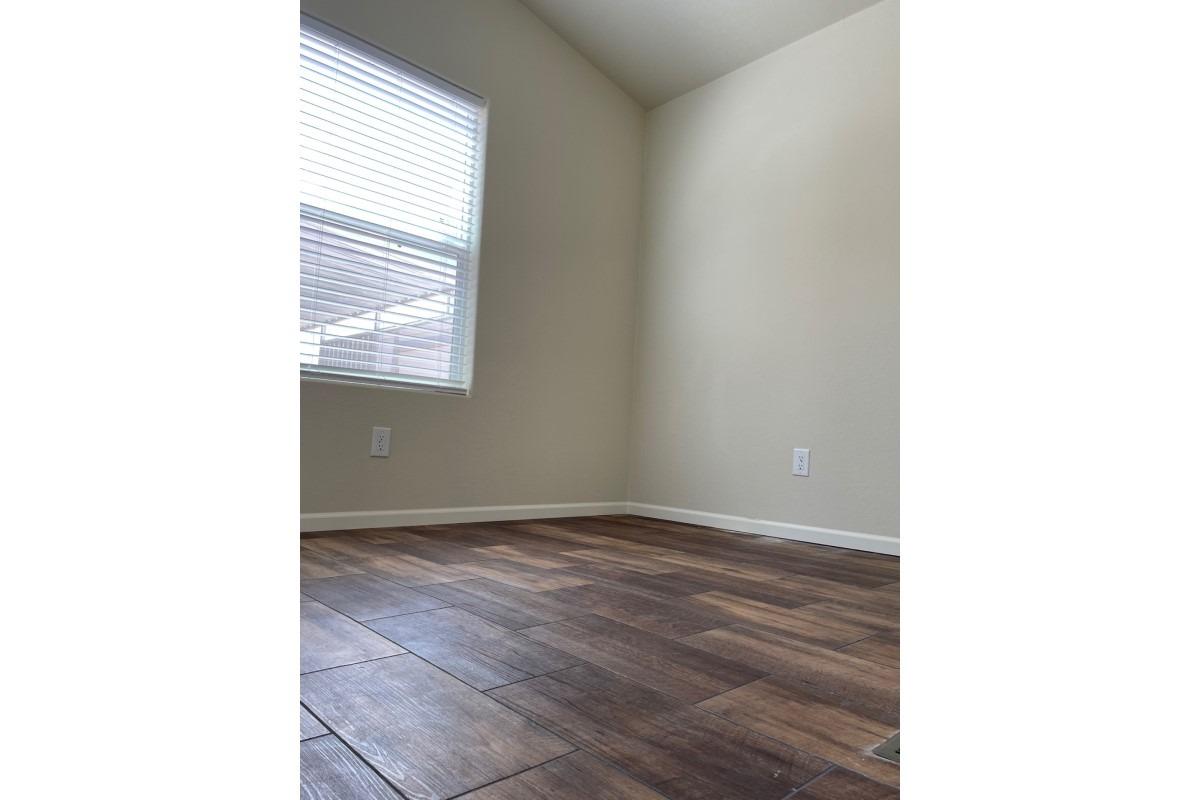 spacious room with window, brown wood-laminate floor
